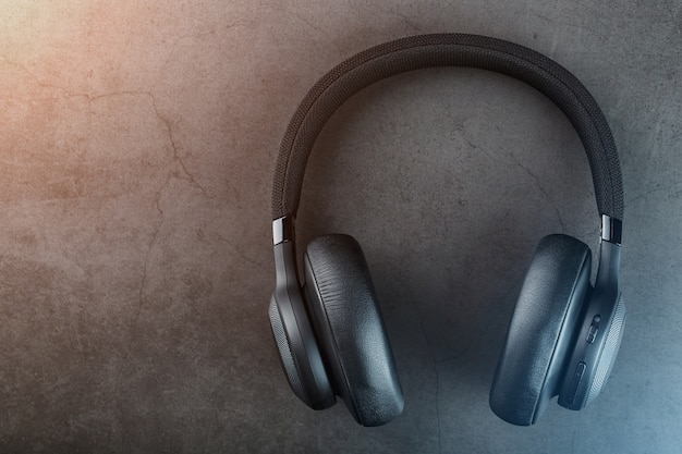 Fones de ouvido pretos sem fio em um fundo escuro com luz de fundo azul e laranja
