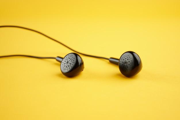 Fones de ouvido pretos sobre amarelo. foco suave. fechar-se. conceito de música. simples