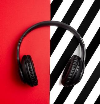 Fones de ouvido pretos sobre um fundo vermelho. conceito mínimo. postura plana.