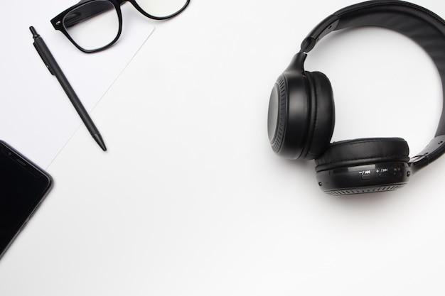 Fones de ouvido pretos, telefone celular e caneta na mesa branca