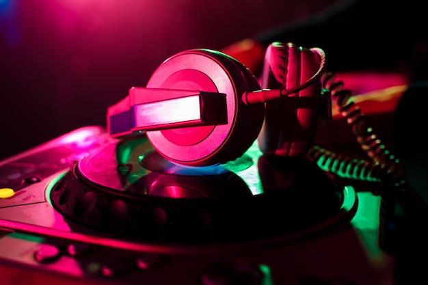Fones de ouvido profissionais e mixer dj para música na boate