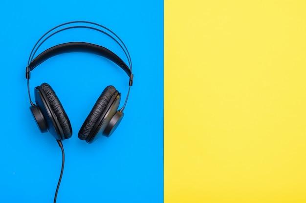 Fones de ouvido profissionais pretos com fio em azul e em amarelo.