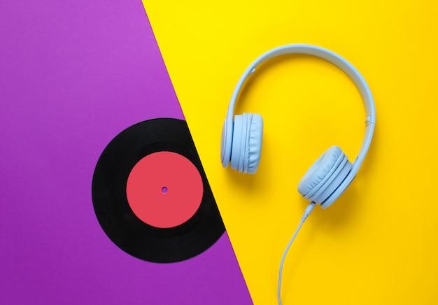 Fones de ouvido, registro lp em fundo amarelo roxo.