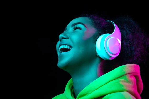 Fones de ouvido. retrato de uma mulher afro-americana isolado no fundo escuro do estúdio em luz de néon multicolorida. lindo modelo feminino. conceito de emoções humanas, expressão facial, vendas, anúncio, moda.