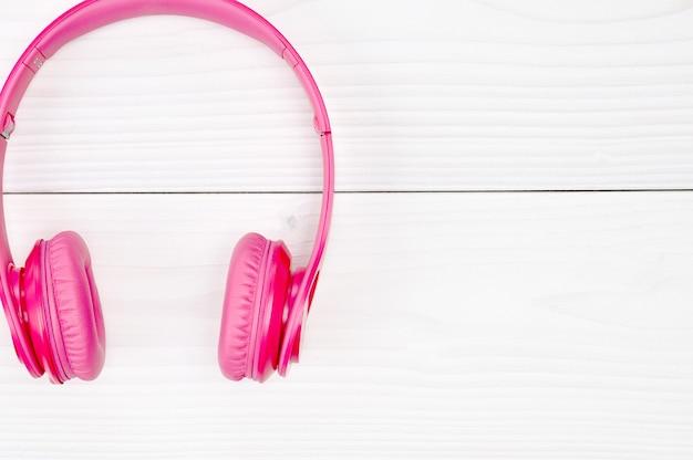 Fones de ouvido rosa para ouvir som e música em uma mesa de madeira branca
