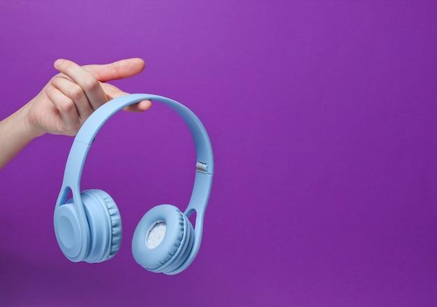 Fones de ouvido sem fio azuis modernos no dedo da mão feminina em um fundo roxo
