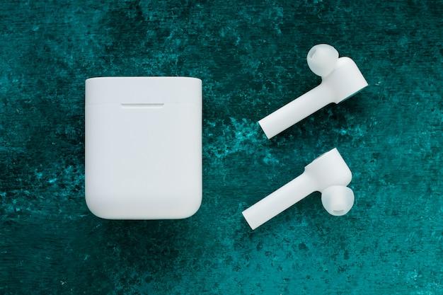 Fones de ouvido sem fio bluetooth branco com caixa de carregamento em verde grunge pintado fundo.