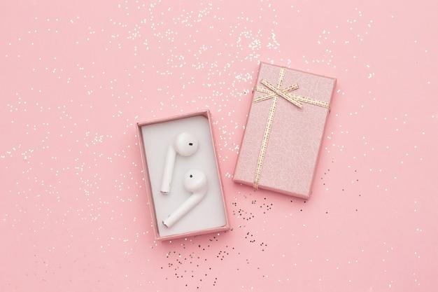 Fones de ouvido sem fio bluetooth brancos em caixa de presente e glitter confetes em fundo rosa