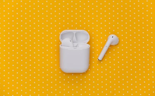 Fones de ouvido sem fio brancos com estojo de carregamento em fundo amarelo pontilhado.