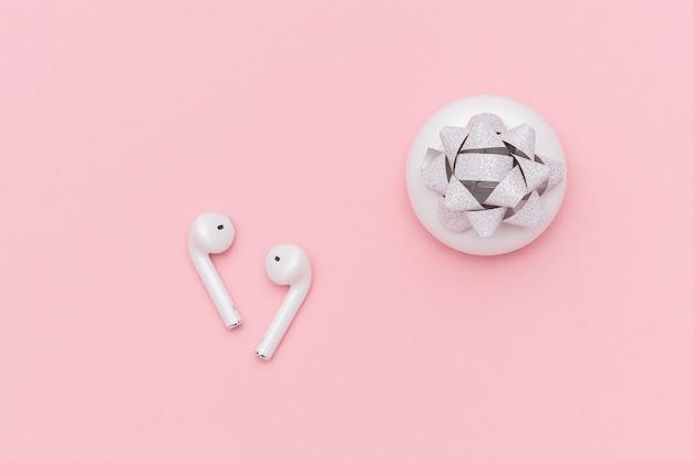 Fones de ouvido sem fio brancos de bluetooth e estojo de carregamento no fundo de papel cor-de-rosa.