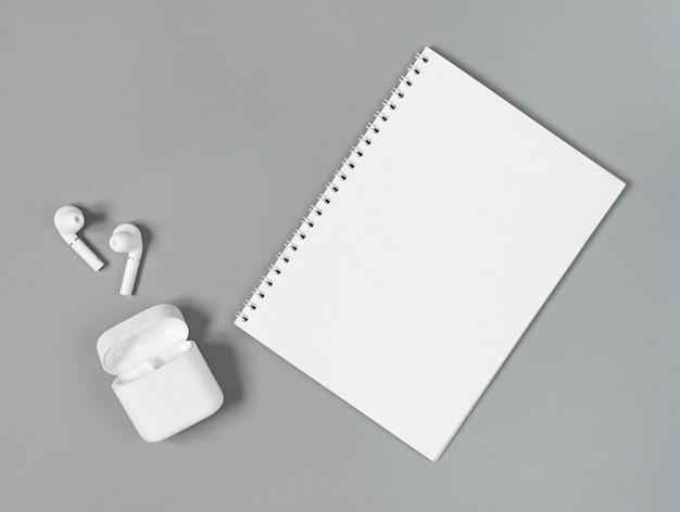 Fones de ouvido sem fio brancos e bloco de notas em uma superfície cinza.