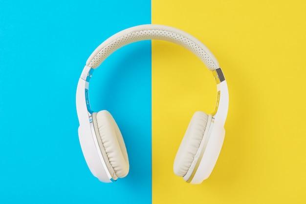 Fones de ouvido sem fio brancos e smartphone em um fundo azul e amarelo