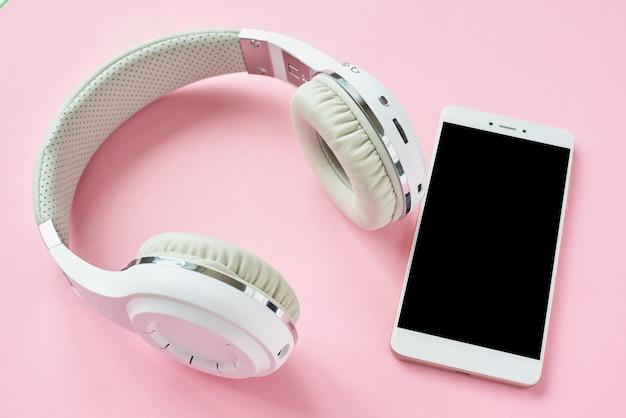Fones de ouvido sem fio brancos e smartphone em um fundo rosa pastel