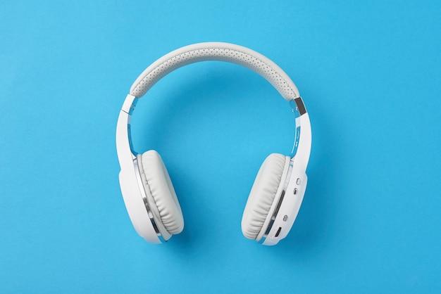Fones de ouvido sem fio brancos em um azul pastel