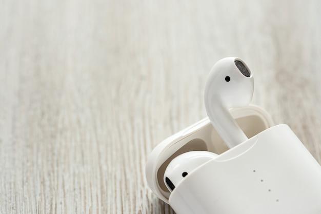 Fones de ouvido sem fio brancos em um estojo de carregamento sobre uma mesa de madeira.