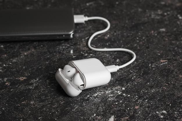 Fones de ouvido sem fio brancos em uma caixa conectada ao banco de energia. acessórios sem fio modernos.