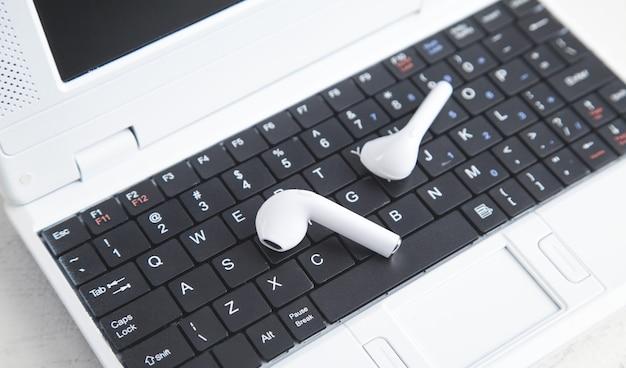 Fones de ouvido sem fio brancos no teclado do laptop.