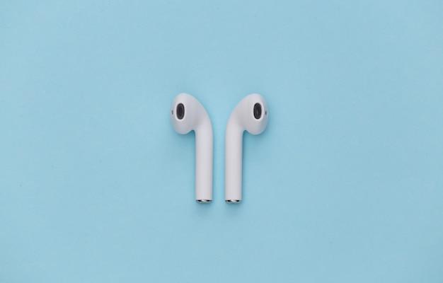 Fones de ouvido sem fio brancos sobre fundo azul.