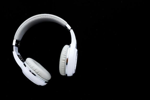 Fones de ouvido sem fio brancos sobre um fundo preto. copie o espaço.