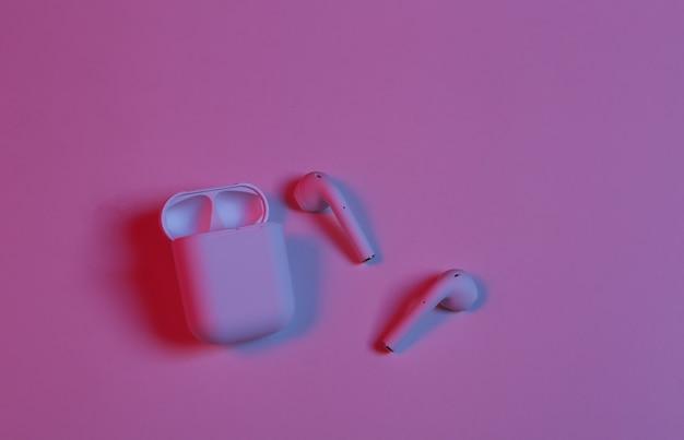 Fones de ouvido sem fio com capa de carregamento em luz neon azul neon vermelho.