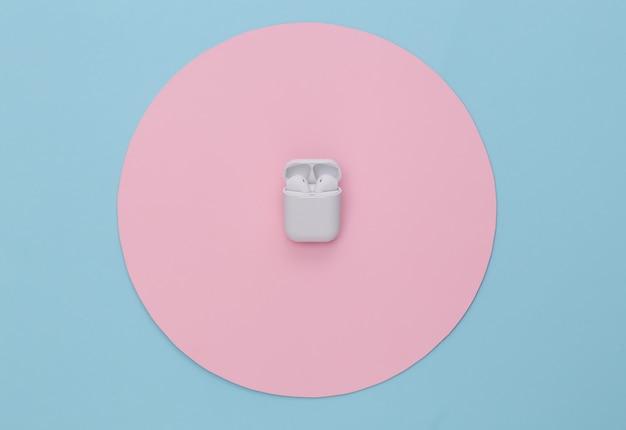 Fones de ouvido sem fio com estojo de carregamento em fundo azul com círculo rosa.