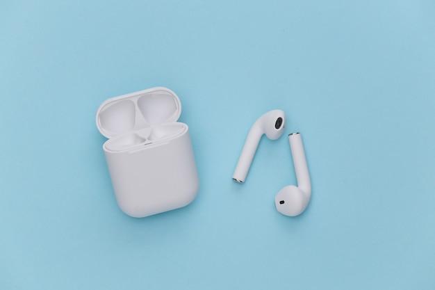 Fones de ouvido sem fio com estojo de carregamento em fundo azul.