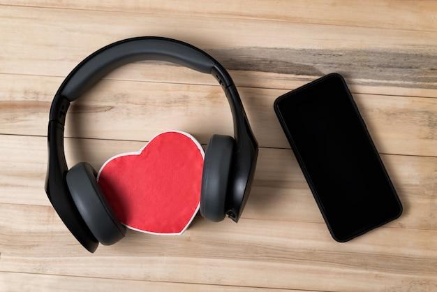Fones de ouvido sem fio de tamanho normal encostados em uma pequena caixa vermelha em forma de coração e smartphone na mesa de madeira marrom clara. diretamente acima
