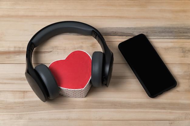 Fones de ouvido sem fio de tamanho normal, encostados em uma pequena caixa vermelha em forma de coração e smartphone na mesa de madeira marrom clara