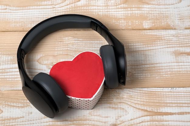 Fones de ouvido sem fio de tamanho normal, encostados em uma pequena caixa vermelha em forma de coração em uma mesa de madeira marrom clara. amo o conceito de música