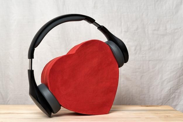 Fones de ouvido sem fio de tamanho normal, usando uma caixa vermelha em forma de coração. amo o conceito de música. vista frontal