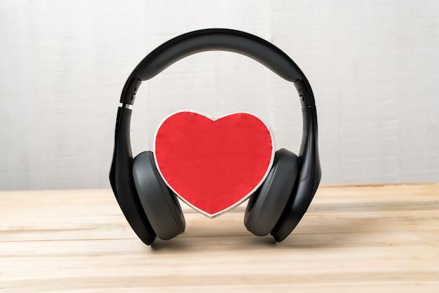 Fones de ouvido sem fio de tamanho normal, usando uma pequena caixa vermelha em forma de coração. amo o conceito de música. vista frontal