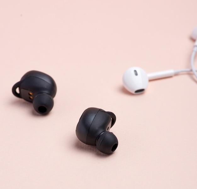 Fones de ouvido sem fio e brancos pretos com fio em bege