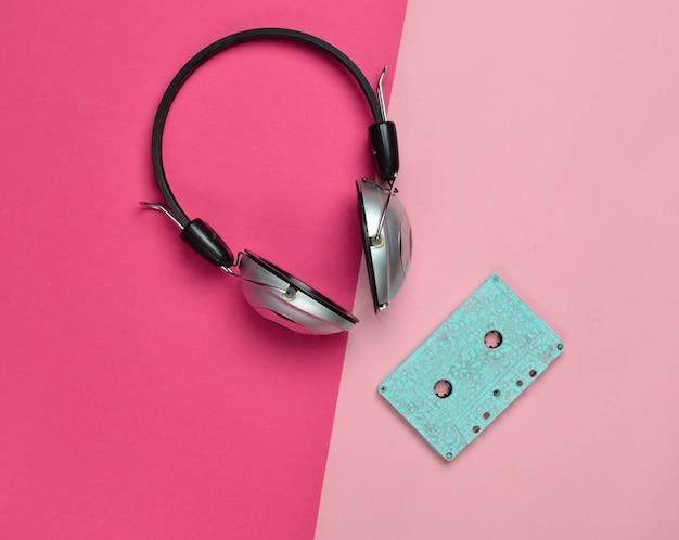 Fones de ouvido sem fio e cassetes de áudio. arte criativa mínima. vibrações retrô musicais. vista do topo.