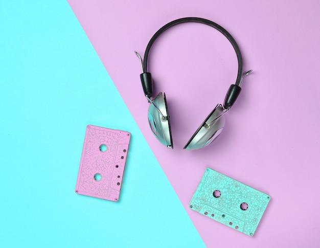 Fones de ouvido sem fio e cassetes de áudio em um papel pastel multicolorido.
