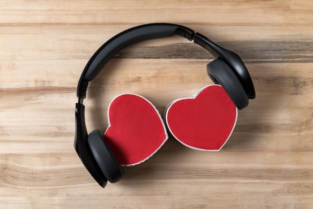 Fones de ouvido sem fio e duas caixas em forma de coração com fundo de madeira. música de corações. diretamente acima.
