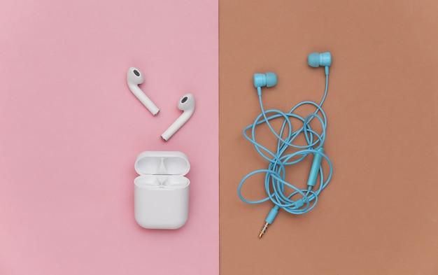 Fones de ouvido sem fio e fones de ouvido emaranhados com fio em fundo rosa marrom. vista do topo. postura plana