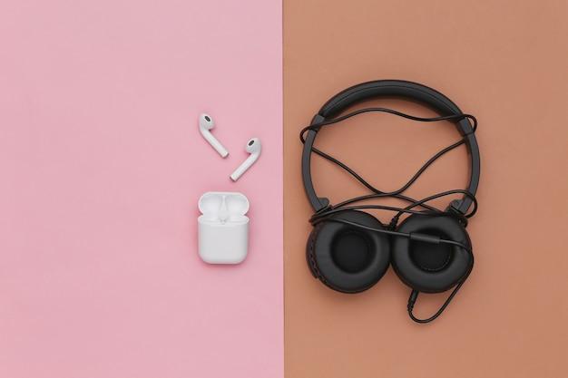 Fones de ouvido sem fio e fones de ouvido estéreo com fio emaranhados em fundo rosa marrom. vista do topo. postura plana