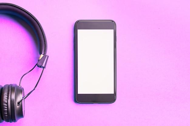 Fones de ouvido sem fio e smartphone em fundo rosa colorido