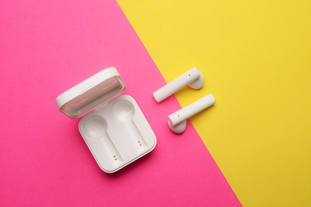 Fones de ouvido sem fio em um fundo rosa. fundo brilhante. fones de ouvido brancos.