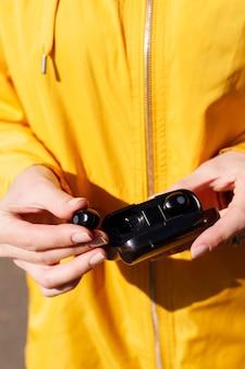 Fones de ouvido sem fio em uma caixa preta nas mãos de uma mulher com uma jaqueta amarela. fechar-se