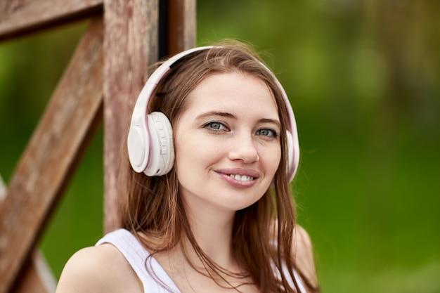 Fones de ouvido sem fio em uma jovem agradável no parque