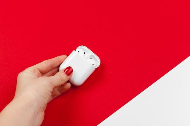 Fones de ouvido sem fio modernos brancos com caixa em vermelho brilhante