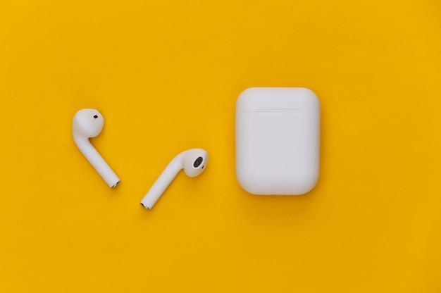 Fones de ouvido sem fio modernos com capa de carregamento em fundo amarelo.