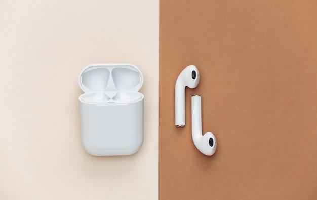 Fones de ouvido sem fio modernos com capa de carregamento em fundo marrom bege.