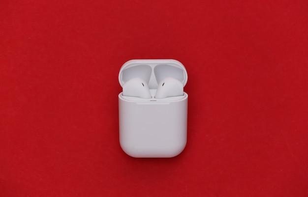 Fones de ouvido sem fio modernos com capa de carregamento em fundo vermelho.