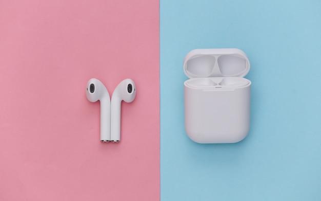 Fones de ouvido sem fio modernos com estojo de carregamento em fundo rosa pastel azul.