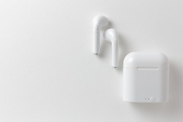 Fones de ouvido sem fio modernos e capa de carregamento em fundo branco, configuração plana
