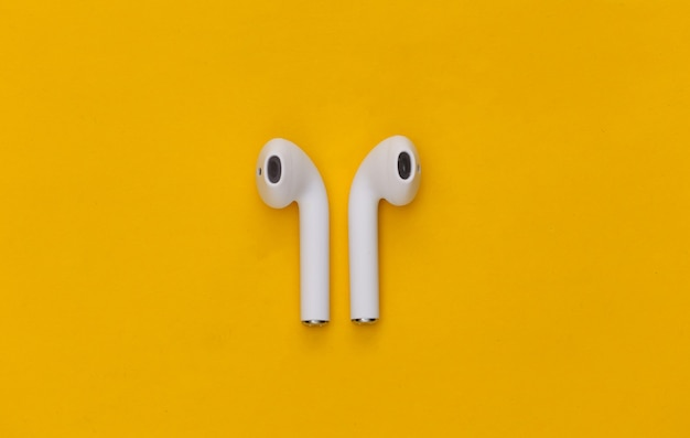 Fones de ouvido sem fio modernos em fundo amarelo.