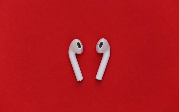Fones de ouvido sem fio modernos sobre fundo vermelho.