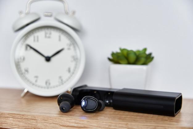 Fones de ouvido sem fio na prateleira com despertador e planta da casa. fones de ouvido no interior do escritório doméstico